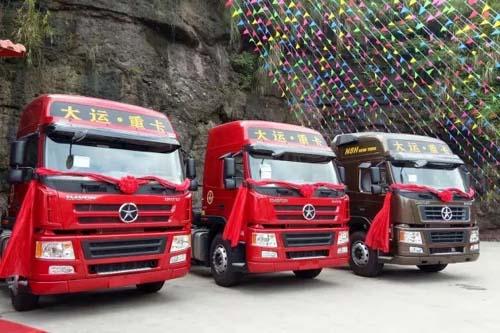 会场门口锣鼓喧天,彩旗飘扬.整齐的大运重卡展车排列在会场门口.